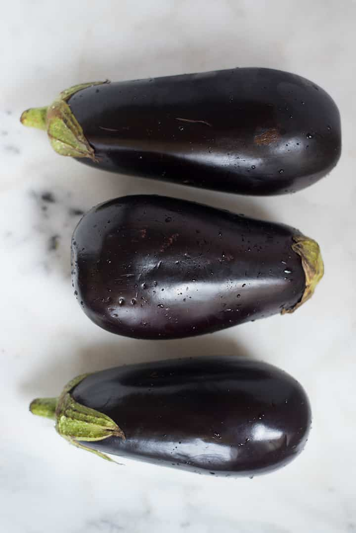 An overhead image of 3 thoroughly washed eggplants on the kitchen counter for the Baked Eggplant Parmesan recipe.