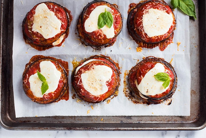 An overhead image of 6 stacks of Baked Eggplant Parmesan on a baking sheet, made with roasted eggplant, homemade tomato sauce, mozzarella and grated parmesan.