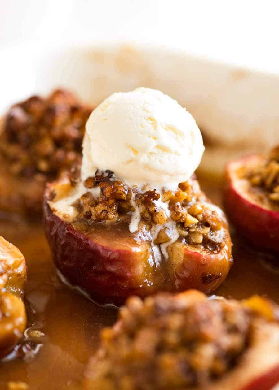 Close up of Caramel Self Saucing Baked Apples with ice cream on top in a baking dish, fresh out of the oven.